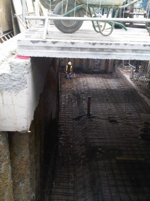 Capping beam is cast on top of piles, and basement is excavated.